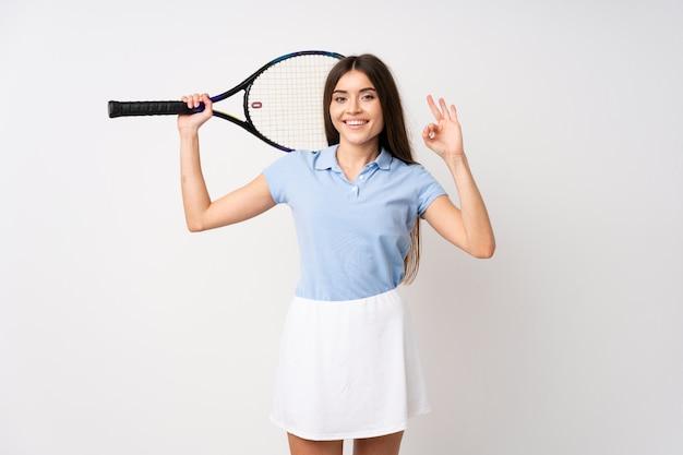 Jeune fille sur un mur blanc isolé, jouer au tennis et faire signe ok