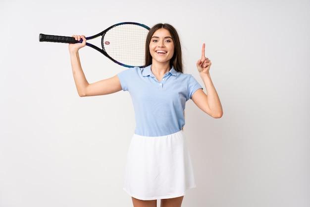 Jeune fille sur un mur blanc isolé, jouer au tennis et pointant vers le haut