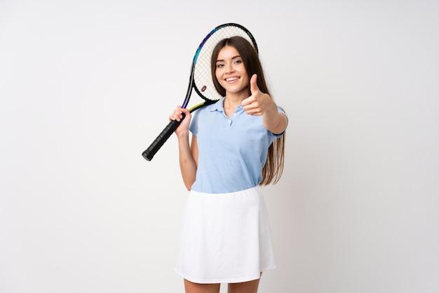 Jeune fille sur un mur blanc isolé, jouer au tennis et avec le pouce vers le haut