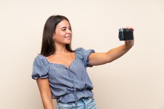 Jeune fille sur mur isolé faisant un selfie