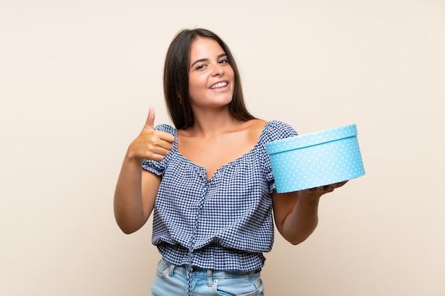 Jeune fille sur mur isolé tenant une boîte-cadeau