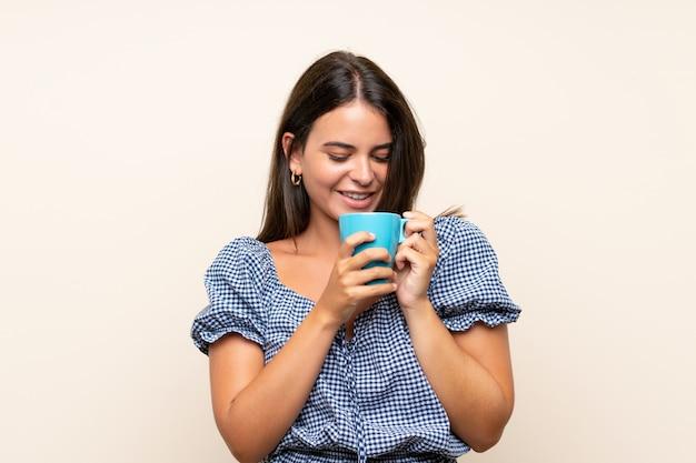 Jeune fille sur un mur isolé tenant une tasse de café