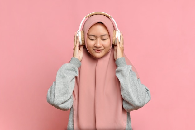 Une jeune fille musulmane écoute sa musique préférée dans des écouteurs blancs, fermant les yeux du plaisir, du plaisir, de l'amateur de musique, sur fond rose