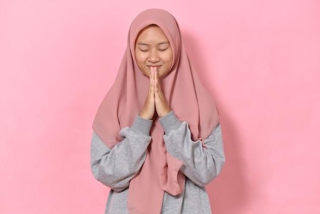 Jeune fille musulmane faisant les mains jointes et fermant les yeux, espace vide isolé sur fond rose