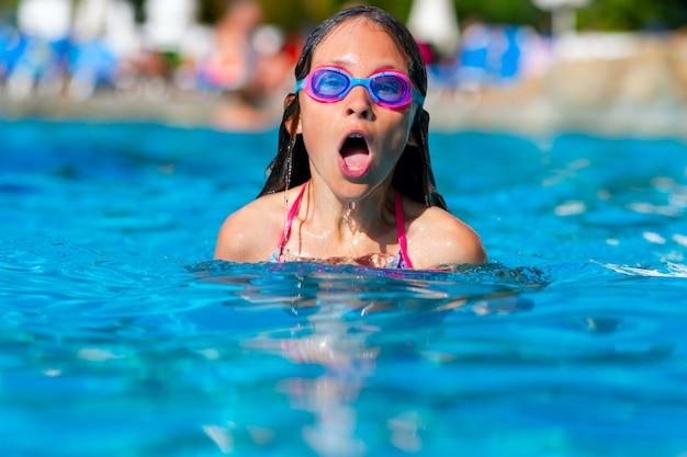 Jeune fille nage nage libre dans la piscine dans des verres. l'adolescent inspire profondément au-dessus de la surface de l'eau.
