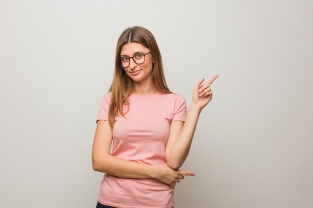 Jeune fille naturelle russe pointant sur le côté avec le doigt