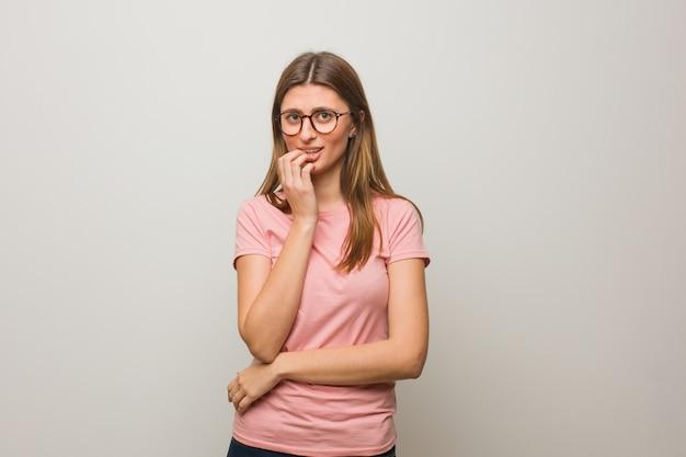 Jeune fille naturelle russe se ronger les ongles, nerveuse et très inquiète