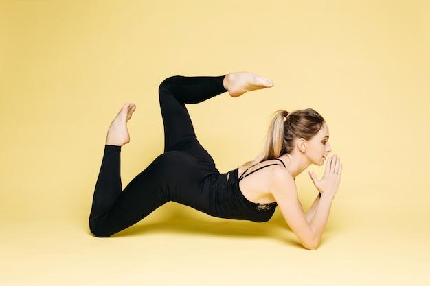Jeune fille en noir faisant des exercices de yoga et en prière.
