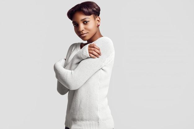 Jeune fille noire belle hipster aux cheveux courts en pull blanc
