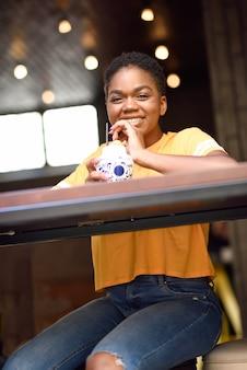Jeune fille noire souriante aux cheveux très courts, buvant un cocktail dans un café urbain.