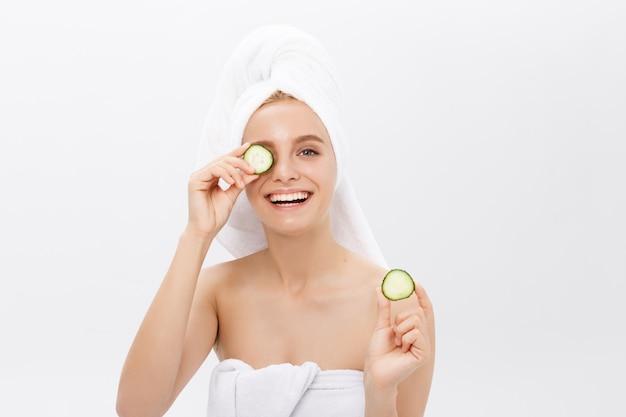 Jeune fille nue belle souriante se cachant les yeux derrière des tranches de concombre sur fond blanc