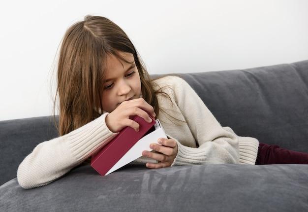 La jeune fille ouvre une boîte avec un smartphone.