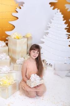 Jeune fille ouvre le cadeau de noël