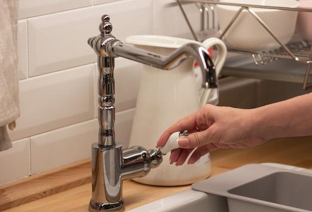 La jeune fille ouvre le robinet pour se laver les mains, concept de santé