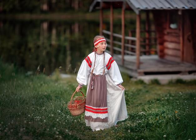Une jeune fille avec un panier de baies de rowan dans ses mains