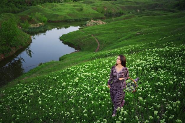 Jeune fille avec un panier de fleurs lors d'une promenade dans une prairie en fleurs