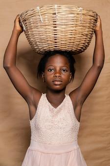 Jeune fille avec panier de paille sur la tête