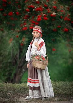 Une jeune fille avec un panier plein d'arbres rowan dans ses mains