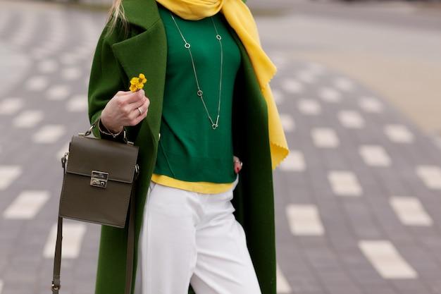 Une jeune fille en pantalon blanc, manteau vert chaud. détails.