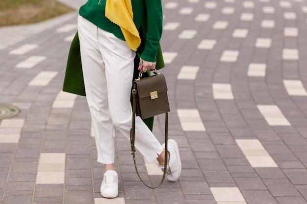 Une jeune fille en pantalon blanc, manteau vert chaud