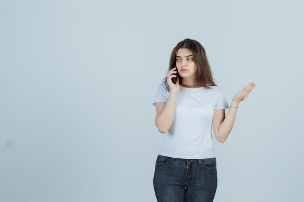 Jeune fille parlant au téléphone mobile en t-shirt, jeans et à la recherche de sérieux. vue de face.