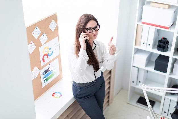 Jeune fille parlant au téléphone et montre une classe de signe.