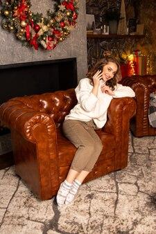 Jeune fille parlant et félicitant par smartphone la veille de noël. elle souriante et assise sur le fauteuil.