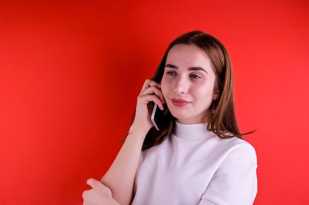 Jeune fille parlant sur un smartphone sur fond rouge. copiez l'espace.