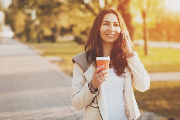 Jeune fille parlant sur un téléphone portable dans le parc