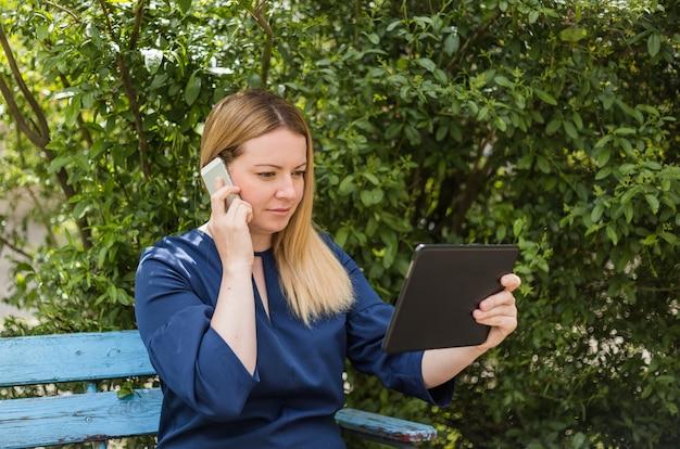 La jeune fille parle au téléphone et tient une tablette assise sur un banc dans le parc.
