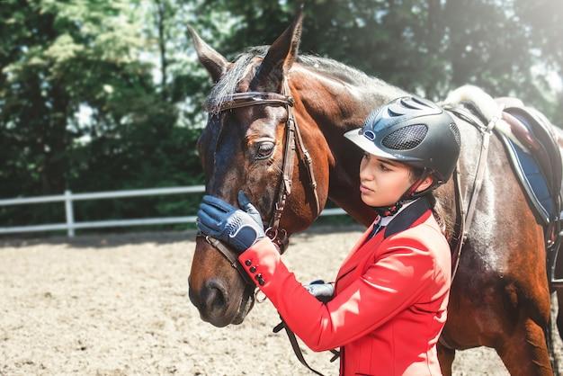 Une jeune fille parle et prend soin de son cheval. elle aime les animaux et passe joyeusement son temps dans leur environnement.