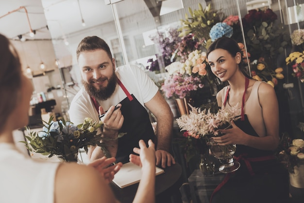 Une jeune fille passe une commande dans un magasin de fleurs
