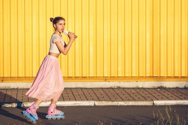 Jeune fille sur le patin à roulettes journée chaude et manger de la crème glacée sur le mur jaune
