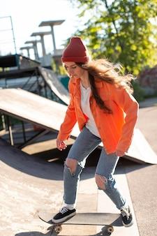 Jeune fille patinage à l'extérieur plein coup