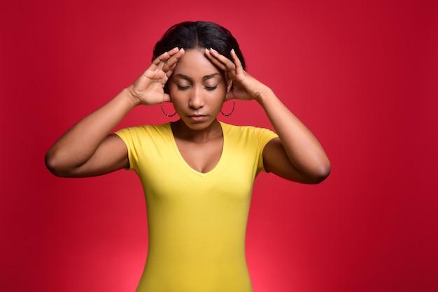 Jeune fille à la peau sombre dans un t-shirt jaune a mal à la tête et tient sa tête dans ses mains.
