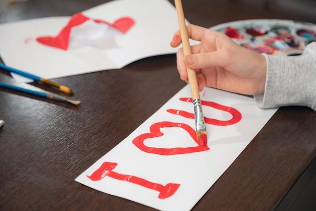 Jeune fille peignant je t'aime avec de la peinture rouge sur papier blanc. gros plan sur la création d'une carte de voeux pour la saint-valentin.