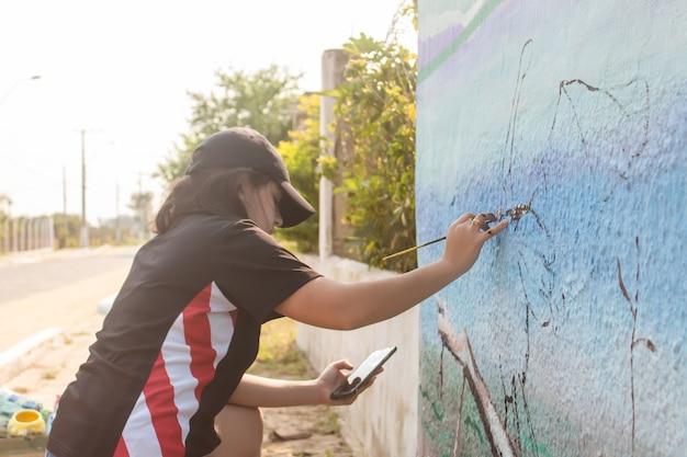 Jeune fille peignant un mur de rue avec son téléphone portable comme référence.