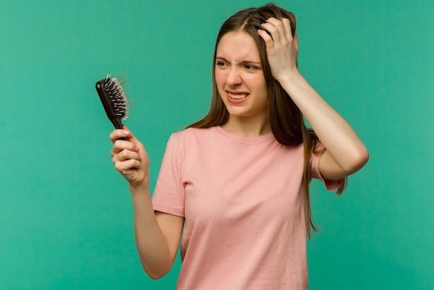 Jeune fille avec un peigne et des problèmes de cheveux sur bleu
