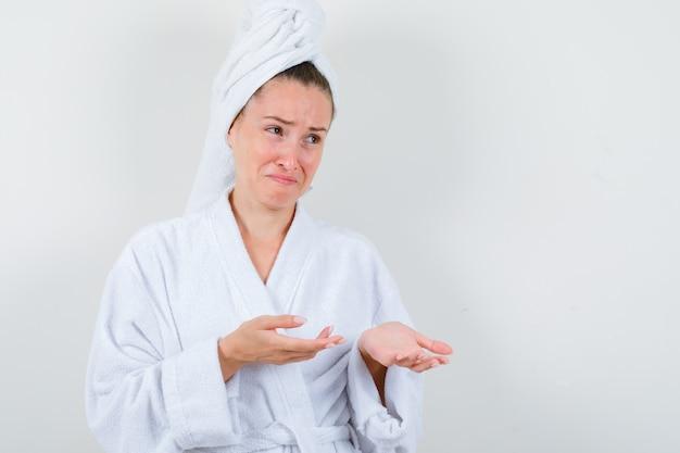 Jeune fille en peignoir blanc, serviette étalant les paumes en pleurant et regardant impuissant, vue de face.