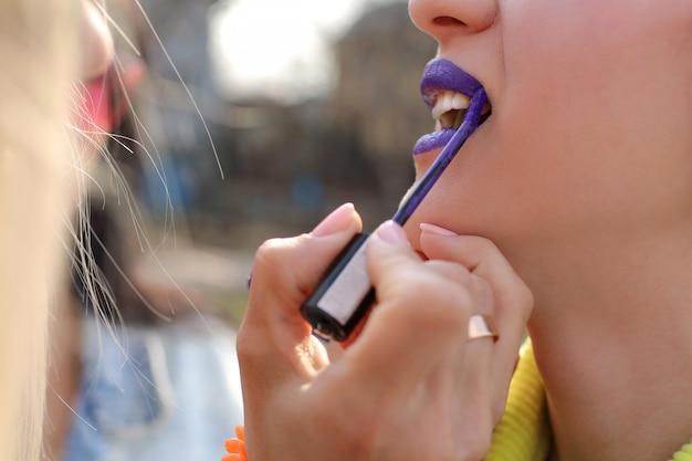 La jeune fille peint son rouge à lèvres violet