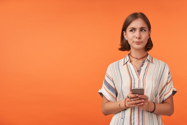 Jeune fille pensant tenant un smartphone, faites un choix, portant une chemise rayée, des accolades et des bracelets.
