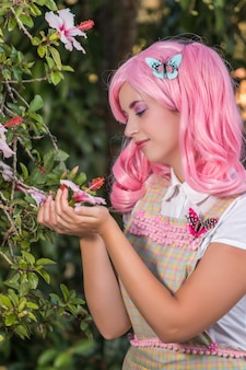 Jeune fille avec une perruque rose posant comme dans le parc