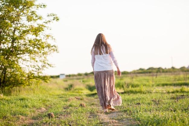 La jeune fille pieds nus dans le champ. le concept de légèreté et sérénité, harmonie avec la nature