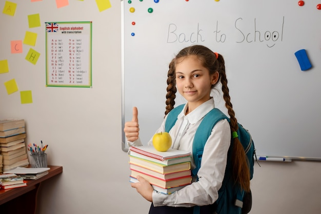 Jeune fille avec une pile de livres apple et un gros sac à dos scolaire debout dans la salle de classe