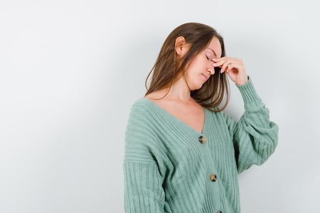 Jeune fille pinçant le pont du nez en maille et à l'ennui. vue de face.