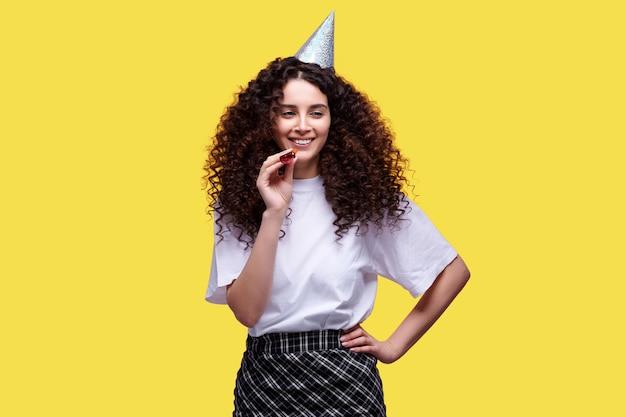 Jeune fille avec pipe et capuchon célébrant l'anniversaire sur fond isolé jaune