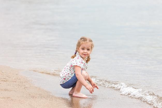 La jeune fille sur la plage de la mer.