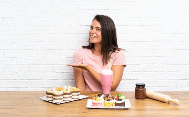 Jeune fille avec plein de mini gâteaux différents qui s'étendent les mains sur le côté pour inviter à venir