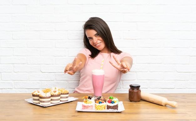 Jeune fille avec plein de mini gâteaux différents souriant et montrant le signe de la victoire