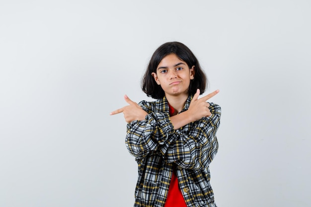 Jeune fille pointant dans des directions opposées en chemise à carreaux et t-shirt rouge et l'air sérieux. vue de face.